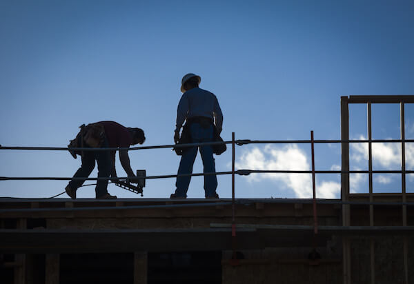 Construction Workers Silhouette on Roof of Building.