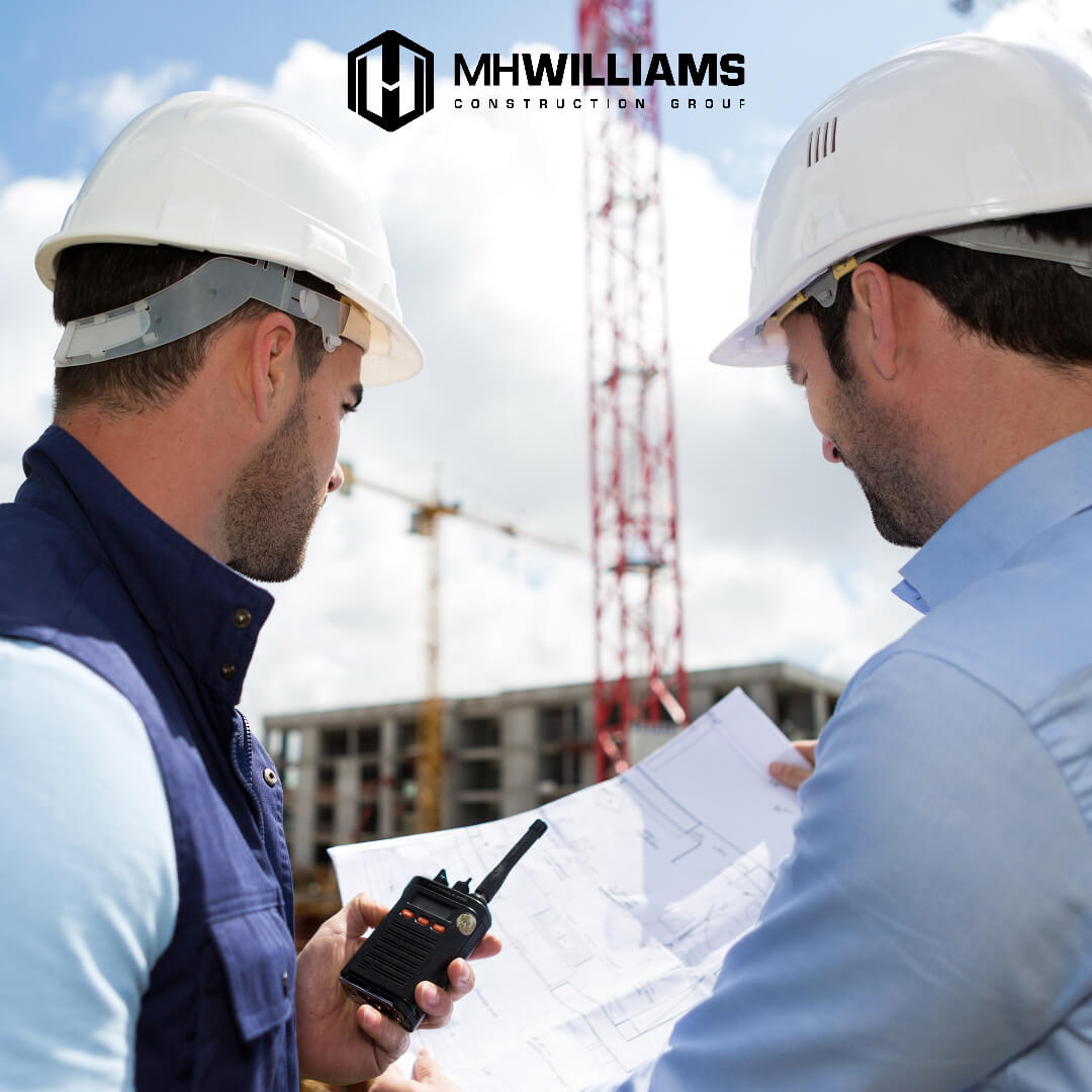 Two contractors reviewing blueprints at construction site