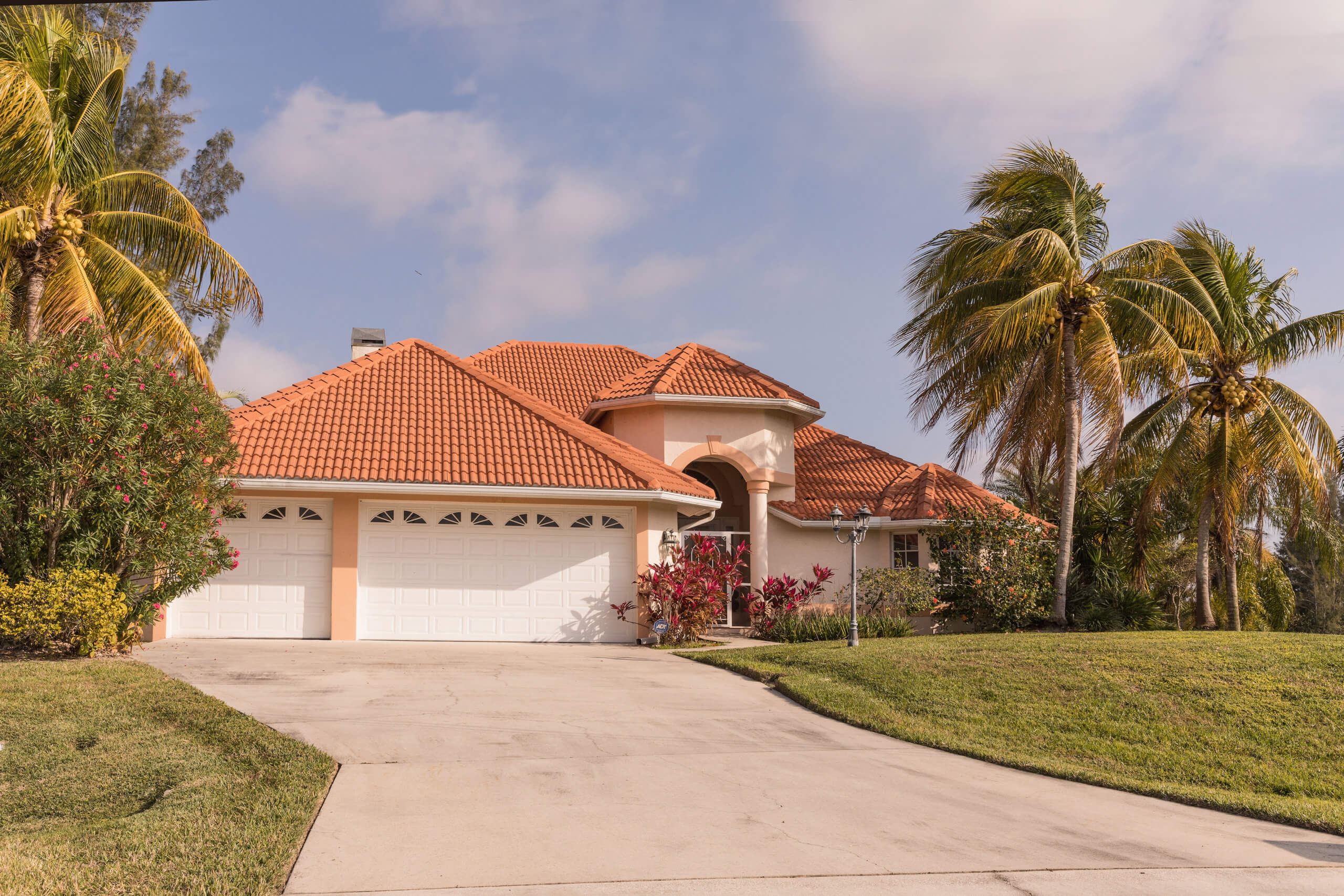 waterproofing your property Typical Southwest Florida concrete block and stucco home in the countryside with palm trees, tropical plants and flowers, grass lawn and pine trees. Florida. South Florida single family house