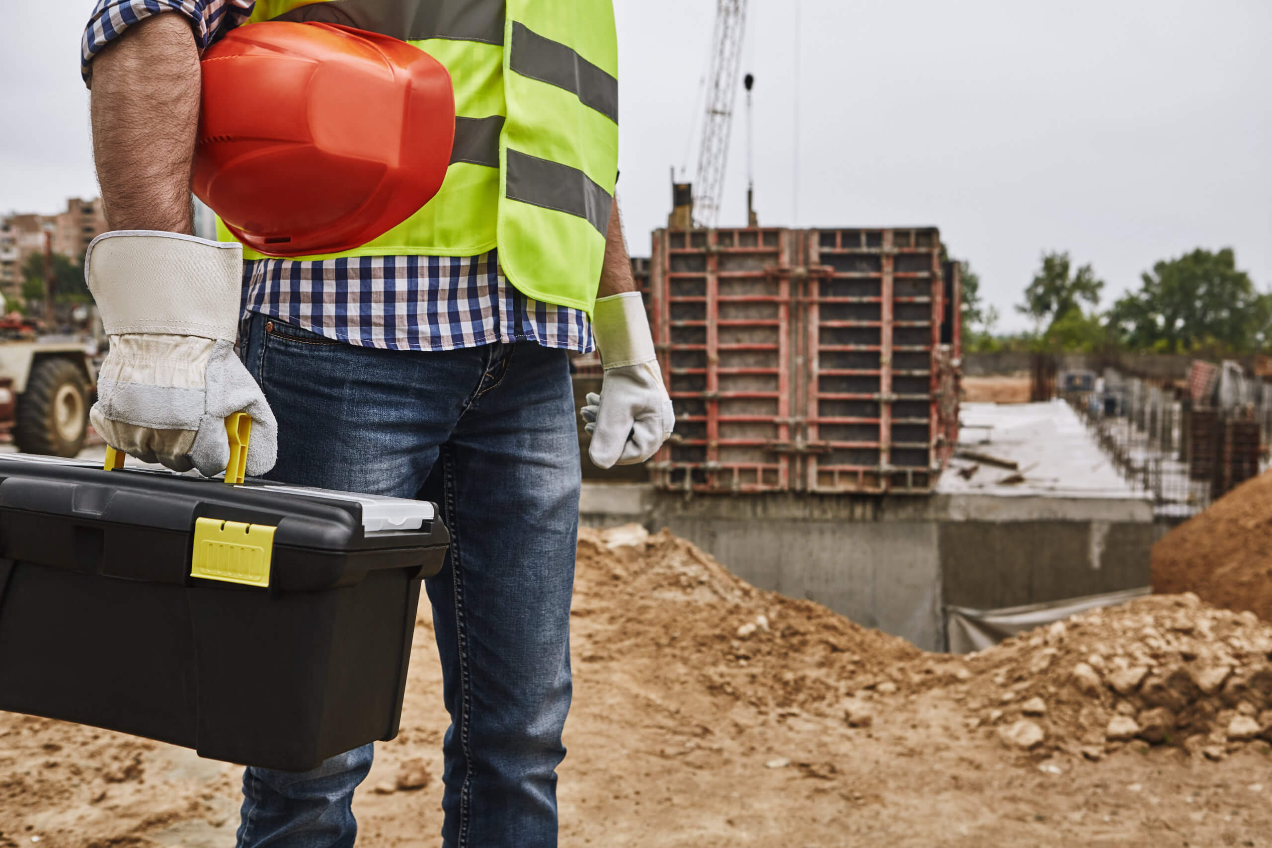 contractor Ready to work! Cropped image of a builder in working uniform holding red helmet and carrying toolbox while standing at construction site. Building concept. Protective gear. Construction concept